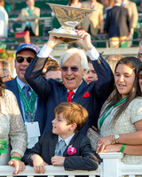 Trainer Bob Baffert raises the Triple Crown trophy in the winner's circle after winning the 147th Belmont Stakes (GI) and the Triple Crown.