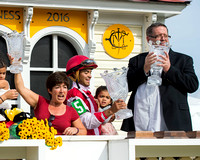 Tammy Fox (left), Luis Saez (center) and Dale Romans (right) celebrate in the Pimlico Cupola winners circle after winning the Black Eyed Susan stakes with Go Maggie Go at Pimlico Race Course in Baltim