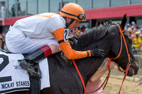 Trevor McCarthy pats Ben's Cat after winning the Jim McKay Turf Sprint stakes for the fifth time in six tries for trainer King Leatherbury at Pimlico Race Course in Baltimore, Maryland.
