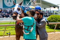 Trevor McCarthy hugs trainer Mario Serey, Jr., after winning the Skipat stakes at Pimlico Race Course in Baltimore, Maryland.